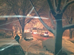 The street looks oddly cozy as the snow weaves a delicate blanket...